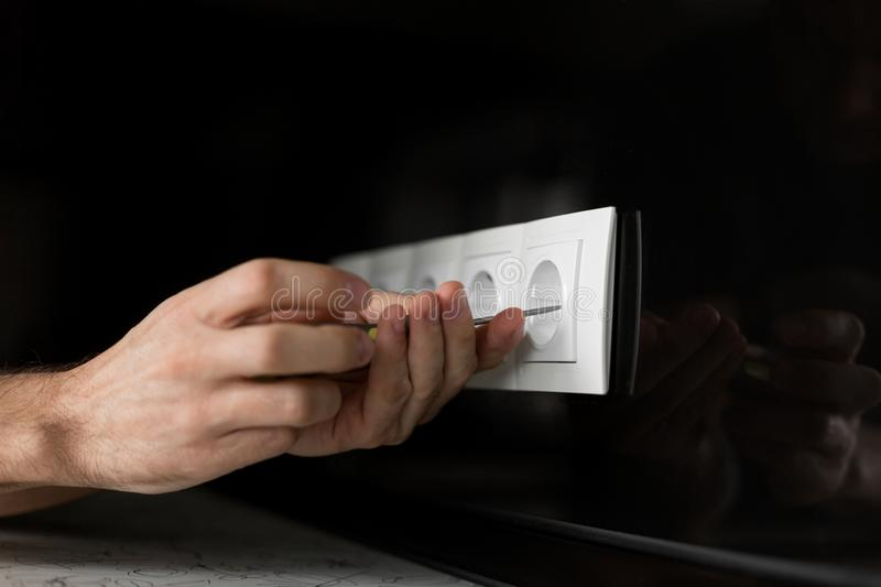 Close-up of an electrician`s hand with a screwdriver disassembling a white electrical outlet on a black glass wall stock image