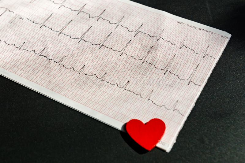 Close up of an electrocardiogram in paper form vith red wooden heart. ECG or EKG paper on black  background.  medical and stock photos