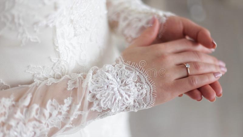 Close up of elegant ring on the finger. Soft and selective focus. Close-up of tender ring on bride`s hand with white stock image