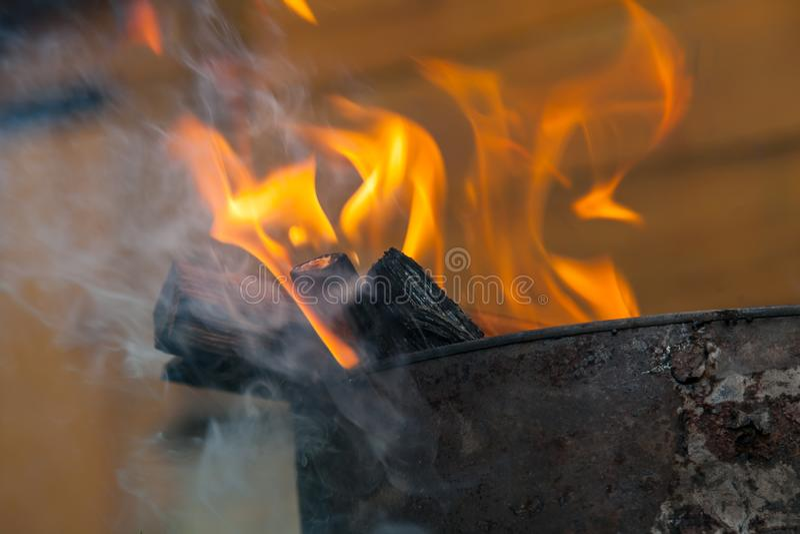 Close-up em um fogo durante um fogo ou em fogo ardente no fundo de uma parede de madeira foto de stock
