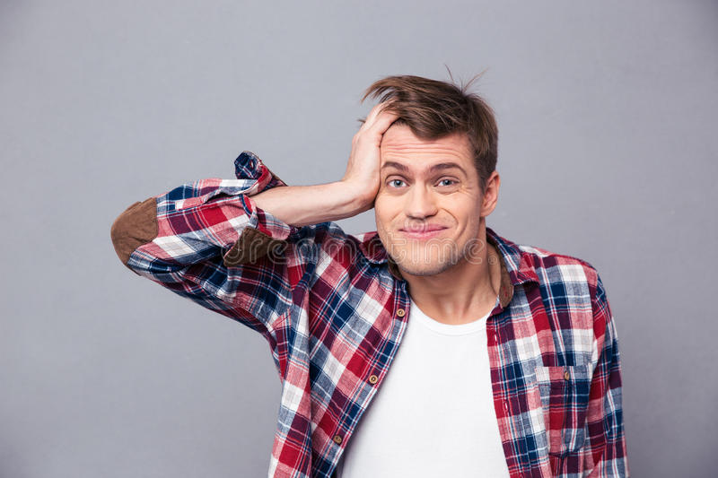 Close up of embarrassed man scratching head and looking confused. Close up of embarrassed young man in checkered shirt scratching head and looking confused over royalty free stock photo