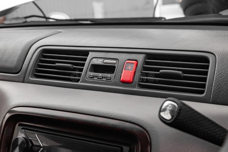 Close-up on emergency button in red color with clock near the duct in the interior of an old Japanese car in gray after dry stock photography