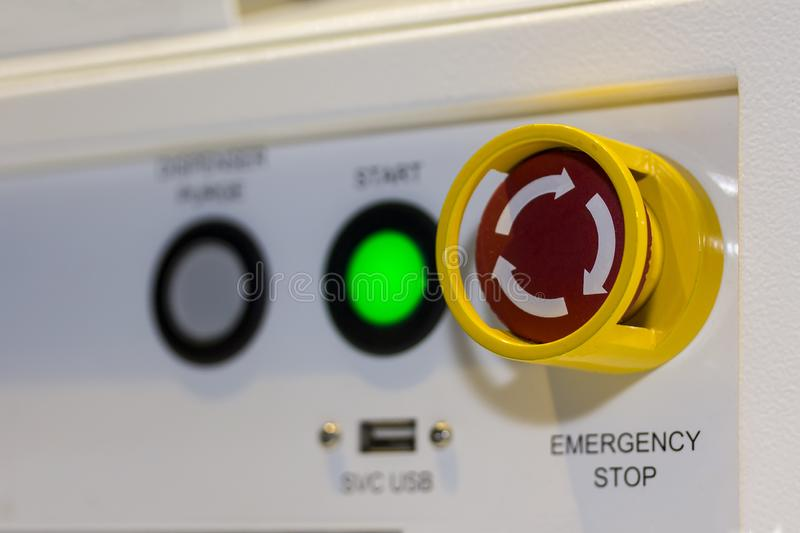 Close up emergency stop button on control panel of machine for safety at factory stock image
