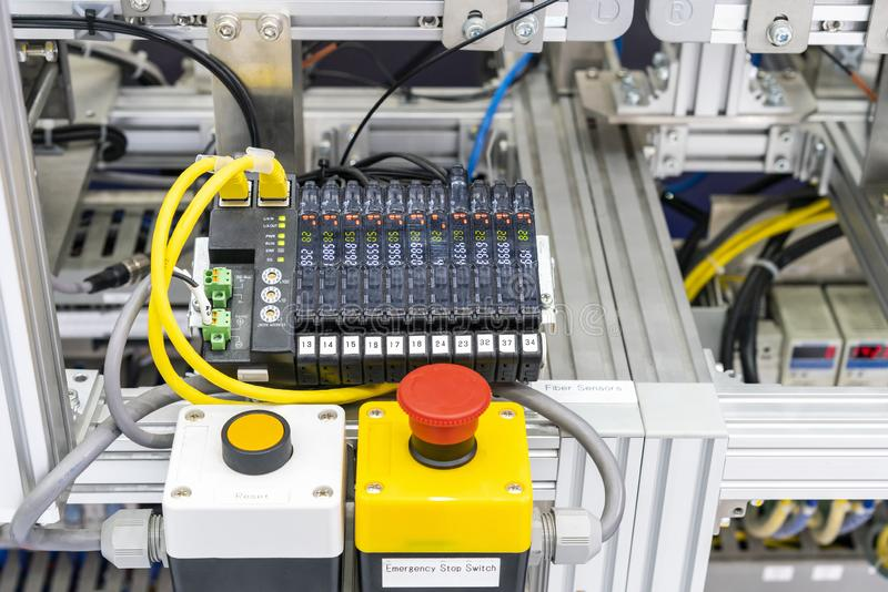 Close up emergency stop switch and Ethernet sensor communication unit with fiber optic cable of high performance automatic. Manufacturing assembly and royalty free stock photography