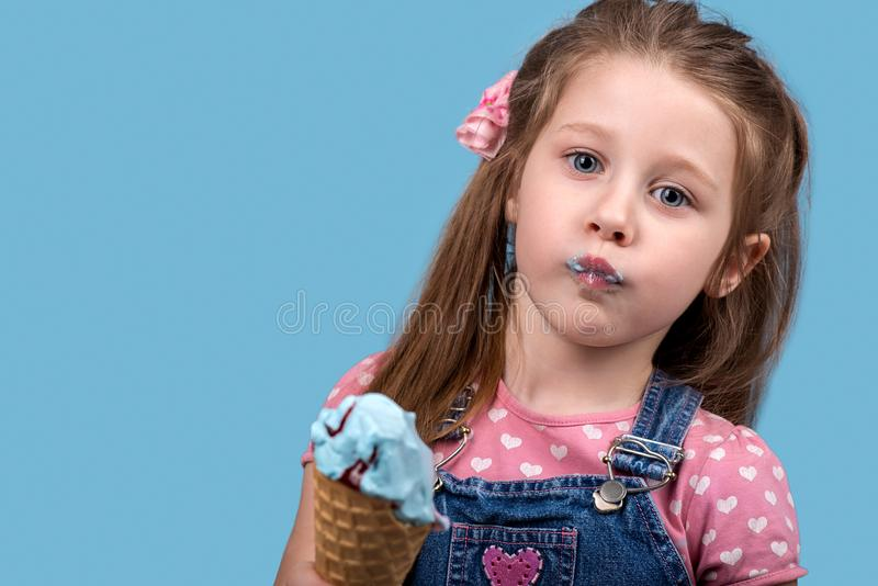 The little girl eats ice cream in wafer gunny on blue backgro. Close up emotional portrait of the little girl on blue background in studio. She cheerfully eats stock photography