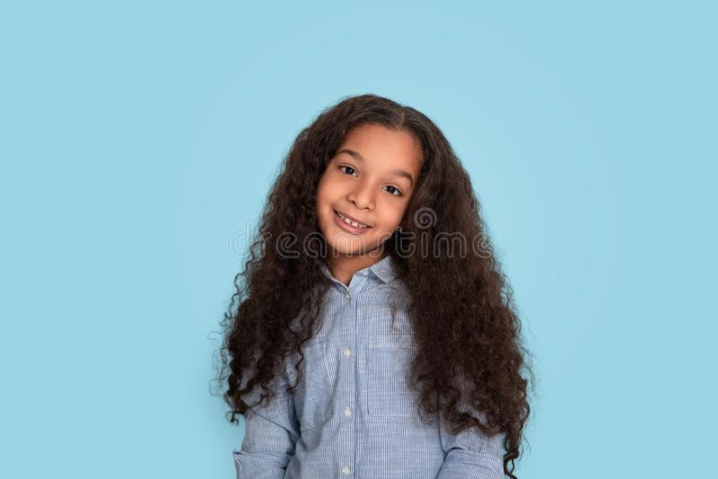 Studio shot of little mulatta frizzy smiling girl wearing blue shirt on blue background. Close up emotional portrait of little mulatta frizzy smiling girl royalty free stock image