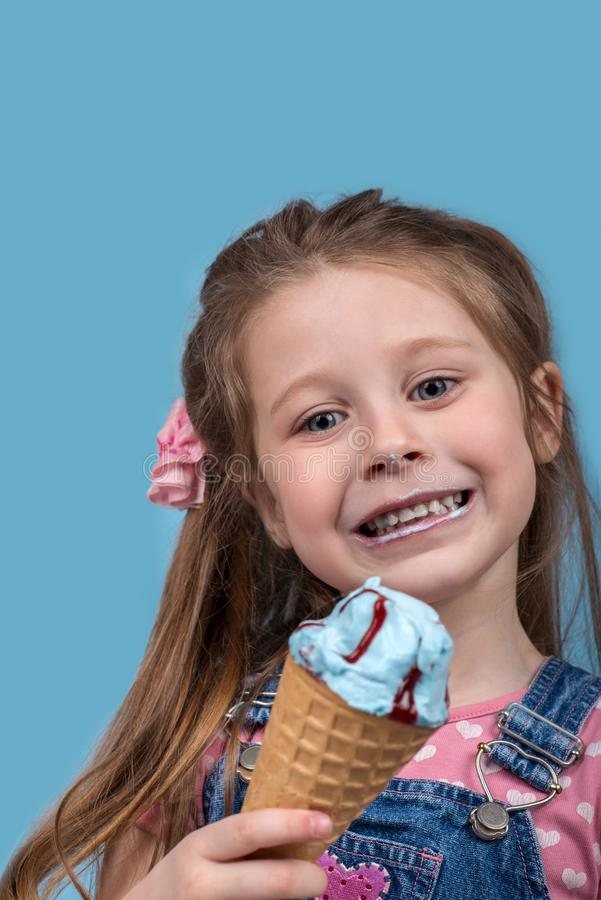 The little girl cheerfully eats ice cream in wafer gunny on bl. Close up emotional portrait of the smiling little girl on blue background in studio. She royalty free stock photography