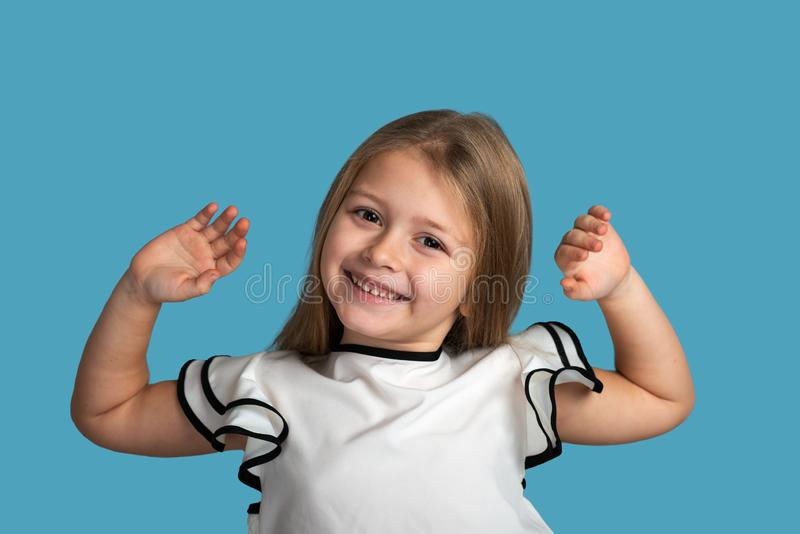 Close up emotional portrait of young blonde smiling girl on blue background in studio. She stock photos