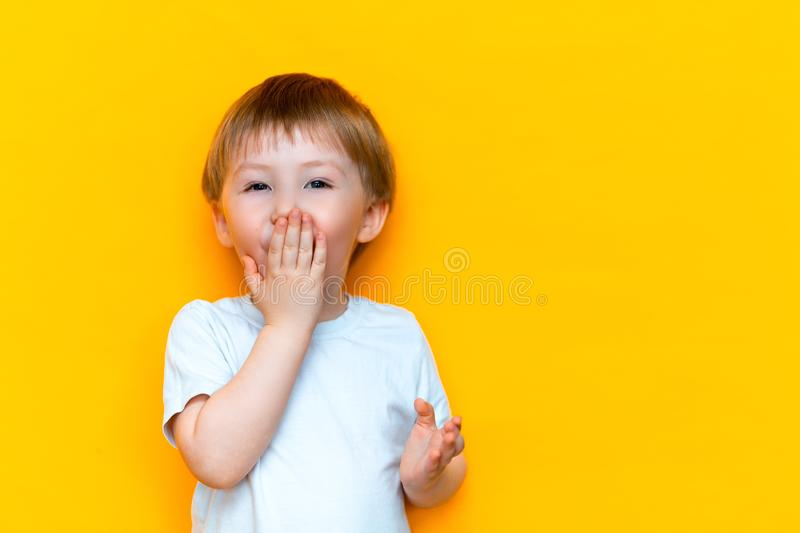 Close up emotional surprised little boy covering mouth with hands isolated on yellow background. blonde hair mixed race asian stock photo