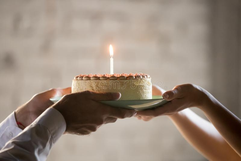 Close up of employee presenting cream pie with candle stock image