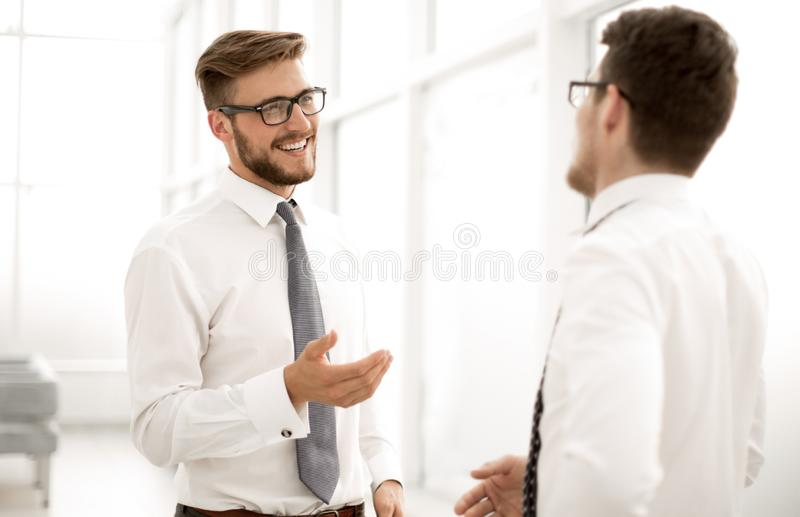 Close up. employees talking, standing near the office window royalty free stock photos