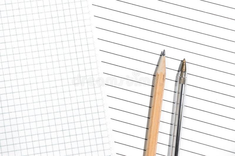 Close-up of empty pages in a cage and in a lined with pencil and pen. The choice of the two options. Top view, copy space royalty free stock photo