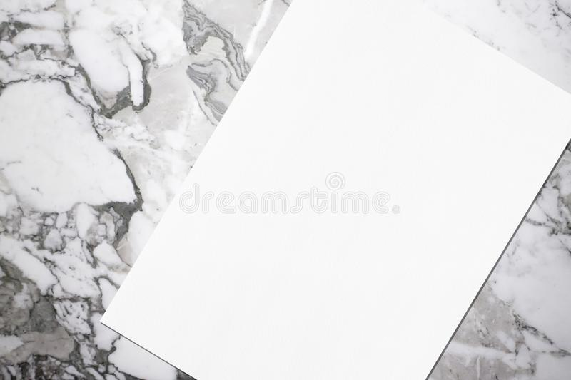 Close up of empty white rectangle poster mockup lying diagonally on grey marble background stock photography