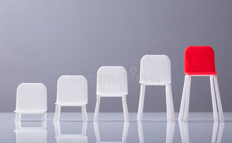 Close-up Of Empty White And Red Chairs In A Row. Increasing Scale Of Empty White And Red Chairs In A Row Against Grey Background stock images