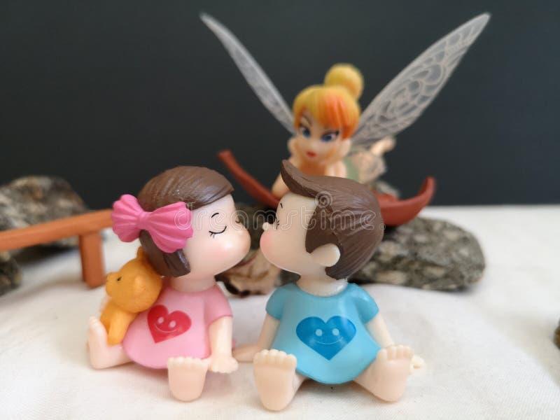 Close-up en macro die van miniatuur kussende babys in de tuin wordt geschoten terwijl fee Tinkerbell die erachter besluipen stock afbeeldingen