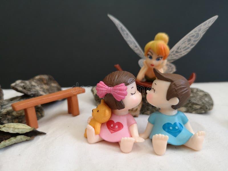 Close-up en macro die van miniatuur kussende babys in de tuin wordt geschoten terwijl fee Tinkerbell die erachter besluipen royalty-vrije stock foto
