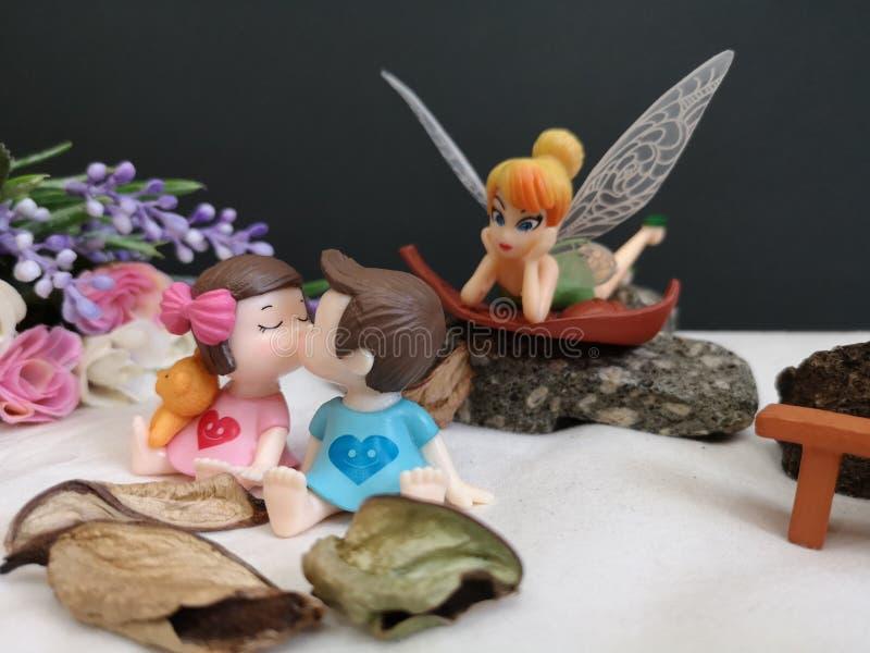 Close-up en macro die van miniatuur kussende babys in de tuin wordt geschoten terwijl fee Tinkerbell die erachter besluipen royalty-vrije stock afbeelding