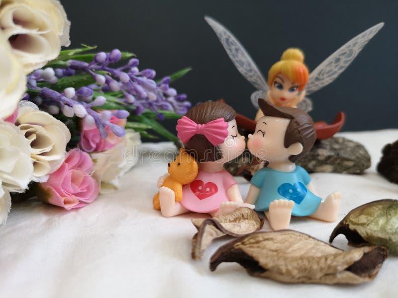Close-up en macro die van miniatuur kussende babys in de tuin wordt geschoten terwijl fee Tinkerbell die erachter besluipen royalty-vrije stock fotografie