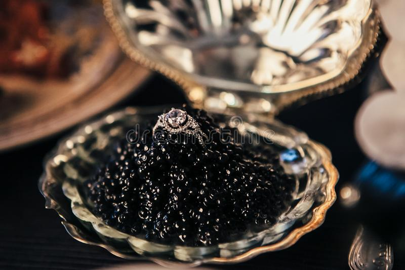 Close-up engagement ring with a huge diamond in a bowl with black caviar, elegant decor for a wedding ceremony, selective focus. Closeup engagement ring with a royalty free stock photo