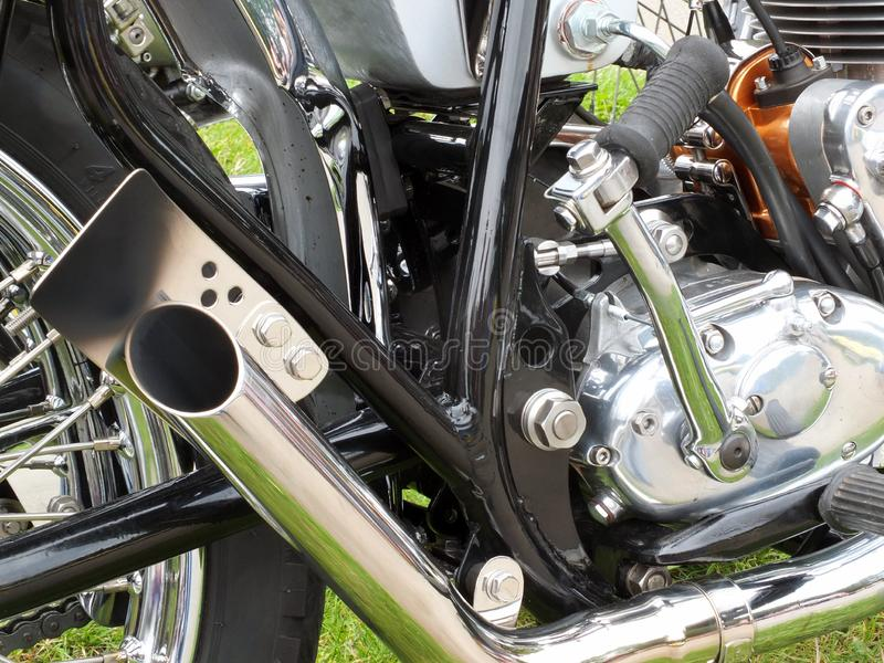 Close up of the engine and chrome exhaust pipe of a vintages custom 1970s scrambler type motorcycle. A close up of the engine and chrome exhaust pipe of a royalty free stock photo