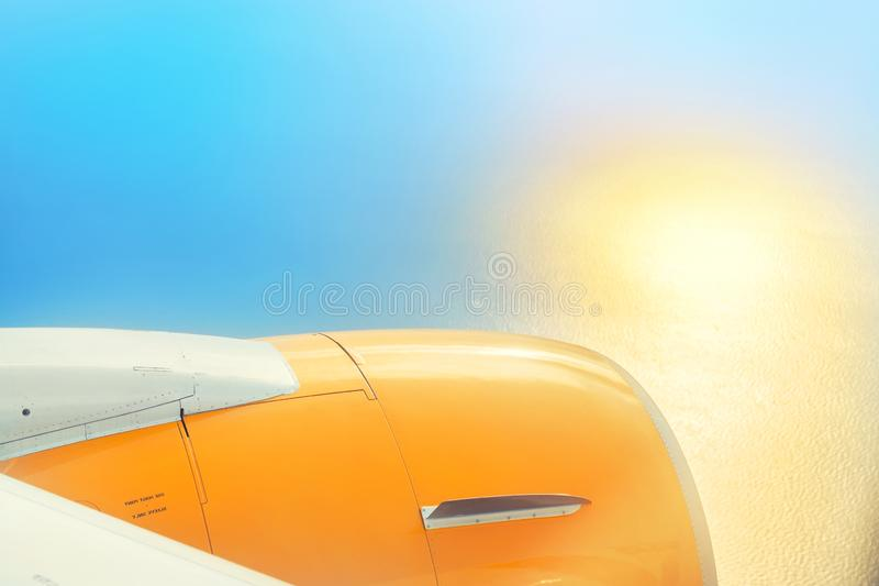 Close-up engine of plane flying over sea or ocean with sun reflection on water surface on bright day or morning. Travel and. Vacation concept, cloud, flight stock photo