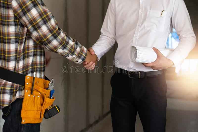 Close up engineer shaking  hand with building contractor in construction site , successful negotiate of manager and industrial stock photo