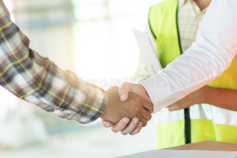 Close up engineer shaking hand with building contractor in construction site , successful negotiate of manager and industrial royalty free stock photos