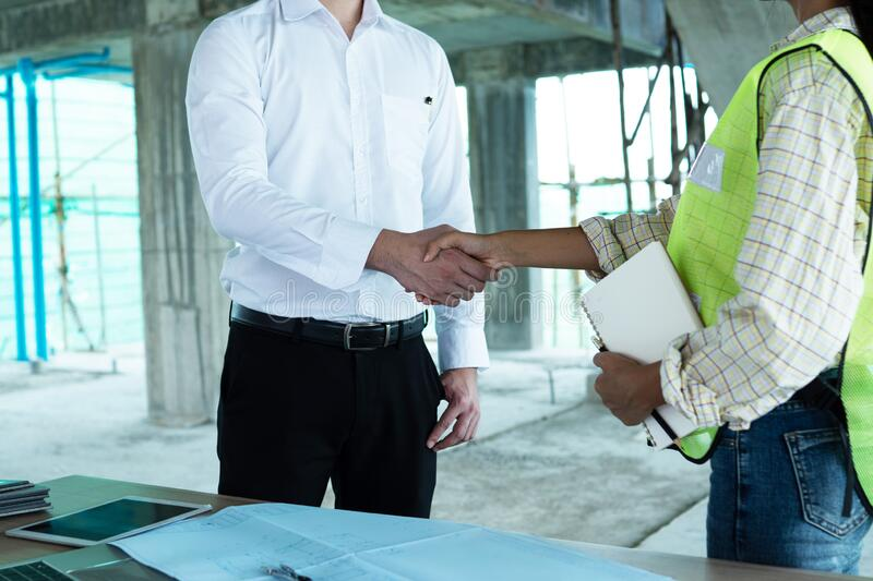 Close up engineer shaking hand with building contractor in construction site , successful negotiate of manager and industrial stock photos