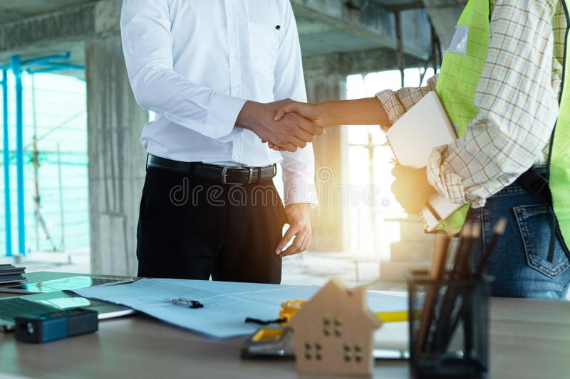 Close up engineer shaking  hand with business man in construction site , successful negotiate of manager and industrial agreement stock photo