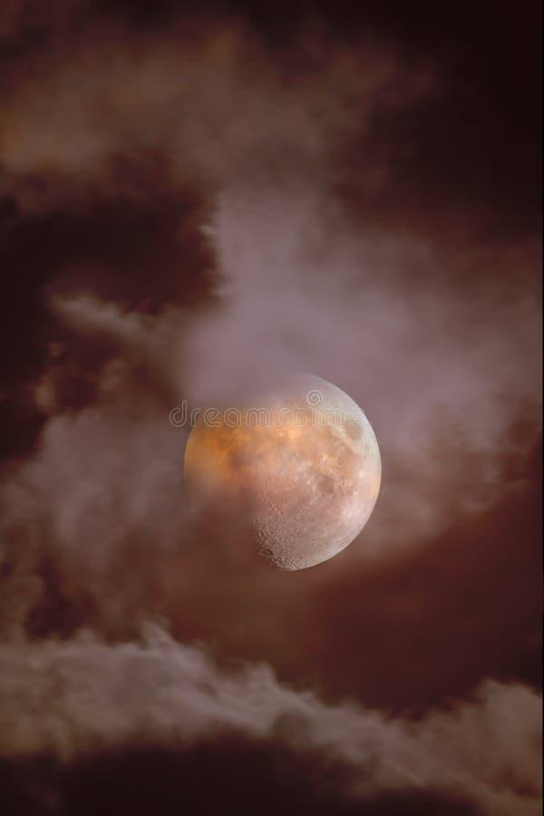 Close-up ensanguentado da lua quando eclipsado contra um fundo das nuvens através de que quebra a luz da lua, vista através do te imagens de stock royalty free