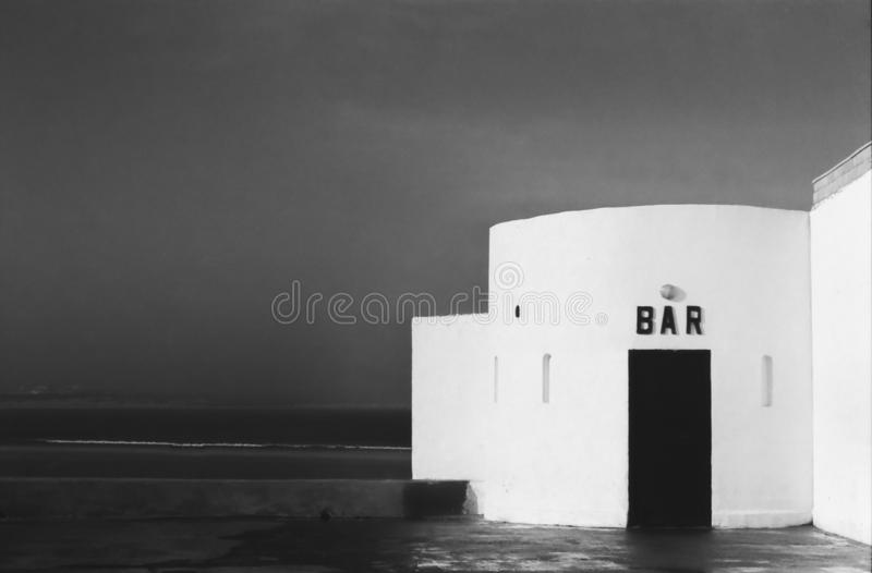 Close up of entrance of isolated nameless bar at the ocean - Black and white vintage photo. royalty free stock photo