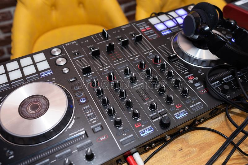 Close-up equipment at the disco in the club. DJ music console, laptops and headphones in bright colors of light in night club bright red-blue background stock photography