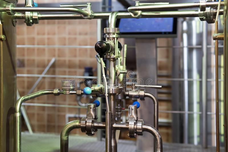 Close up of equipments in modern interior of brewery. Manufacturable process of brewage. Pipes, switchers and tubes junctions in a. N up-to-date brewery. Mode royalty free stock images