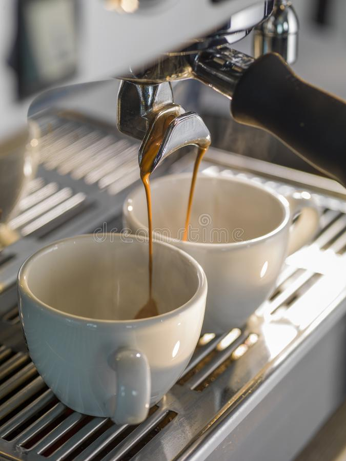Close-up of espresso pouring from coffee machine. Professional coffee brewing stock photography