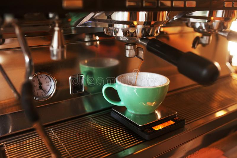 Close-up of espresso pouring from coffee machine. Professional coffee brewing stock image