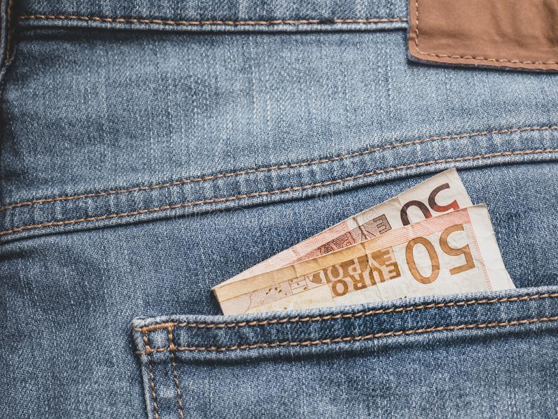 Close up of a 50 euro banknote in a pocket. Close up of a 50 euro banknote in a Jeans pocket finance background bill black blue business cash casual closeup royalty free stock photos