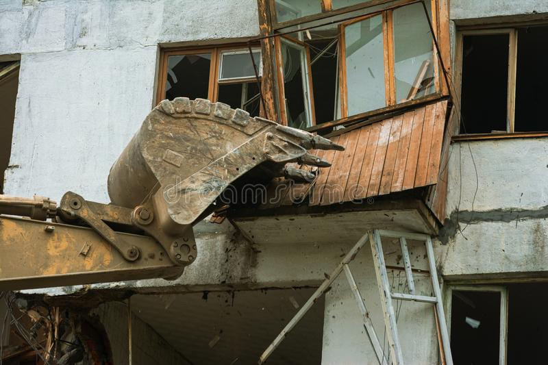 Close-up of an excavator bucket destroys a wooden balcony royalty free stock photos