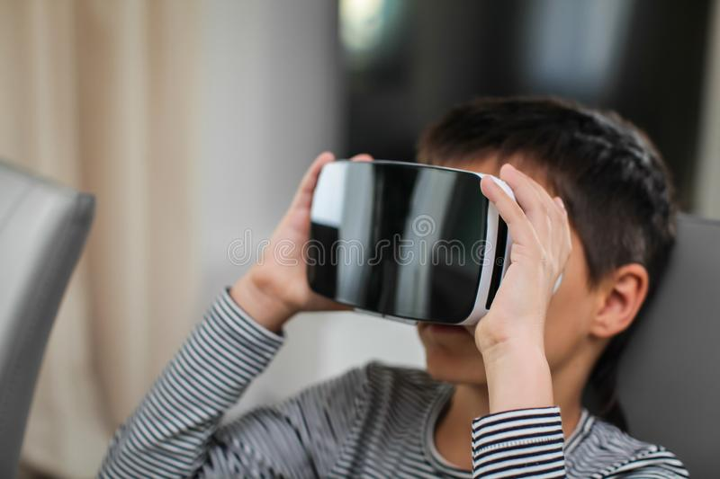Close up Excited little kid using virtual reality glasses. He sits by the table and uses new gadget technology stock photo