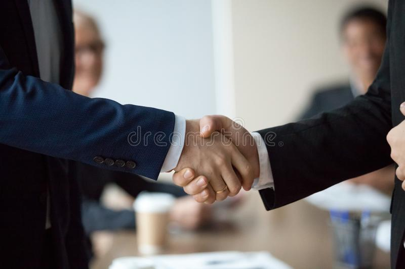 Close up of executive businessmen in suits male hands shake. Close up of two executive businessmen in suits male hands shake, hr hiring and new job, making stock photography