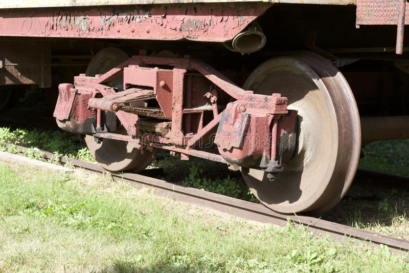 Close up exterior view of the wheels under an old 19th Century railroad train boxcar. Close up exterior view of the wheels under an old weathered red 19th stock photo