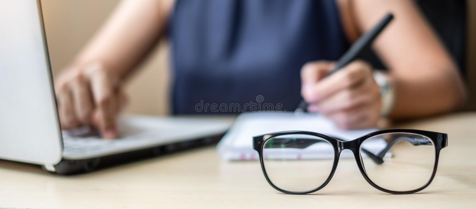 Close up eye glasses with Businesswoman using laptop analysis marketing plan background. Business, Finance and Vision concepts stock photo