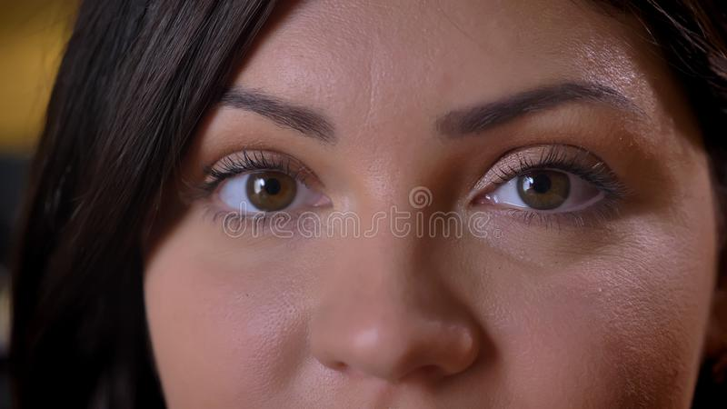 Close-up eye-portrait of beautiful middle-aged overweight woman watching calmly into camera on office background. stock photos