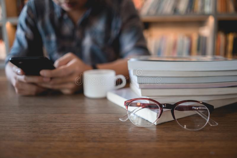Close up eyeglasses and books stack on wooden desk in university or public library with man using mobile phone reading or text stock photo