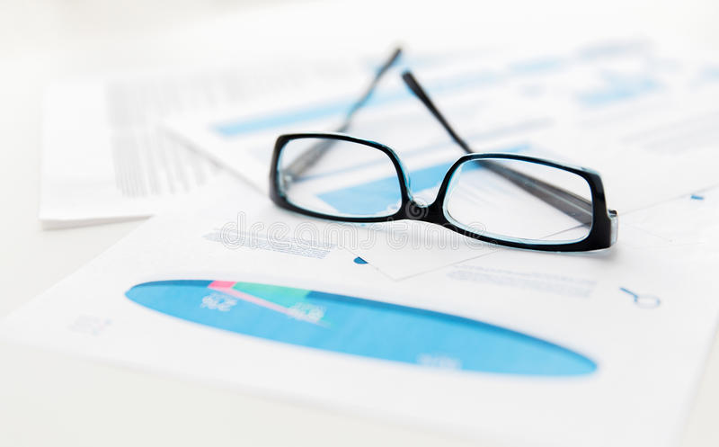 Close up of eyeglasses and files on office table. Business, objects and statistics concept - close up of eyeglasses and files on office table stock image