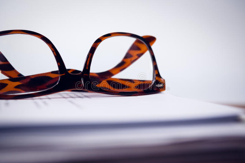 Close up of eyeglasses on paper. At table against wall stock photos