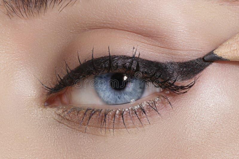 Close up on eyes , making colorful eyeshadows and eyeliner. Tutorial royalty free stock image