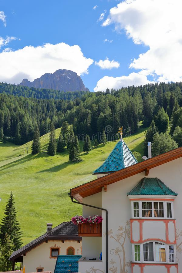 Close-up on a facade in Selva with meadows, forest and Sassolungo mountain in the background, Val Gardena stock photography