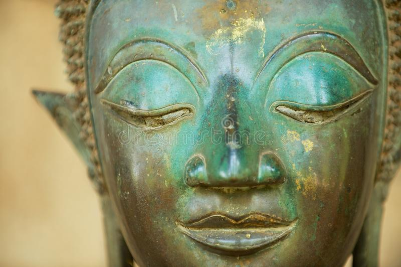 Close-up of a face of an ancient copper Buddha statue in Vientiane, Laos. royalty free stock photo