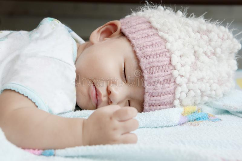 Close up face of baby sleeping on clothes bed wearing wool hood stock photos