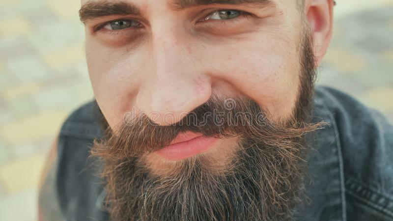 Close-up face of a bearded, brutal and smiling man in the street. stock photos